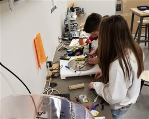 A female and a male student working on a project in a makerspace.