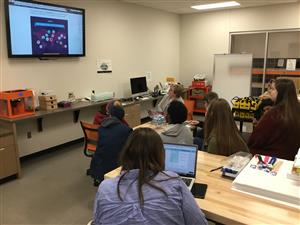 Students in a makerspace, viewing a presentation on a screen about the various tools available.